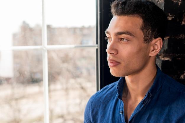 Homem bonito jovem pensativo olhando pela janela Foto gratuita