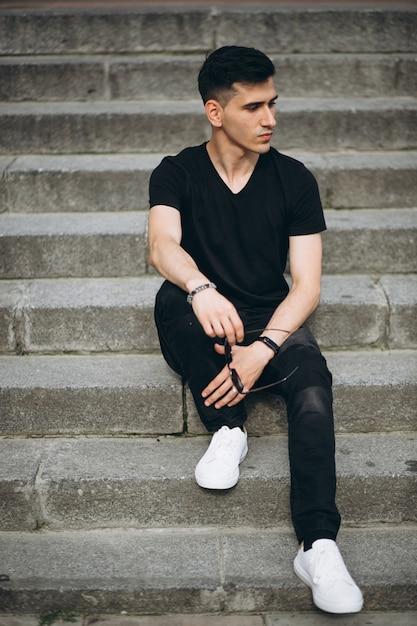 Homem bonito jovem sentado na escada Foto gratuita
