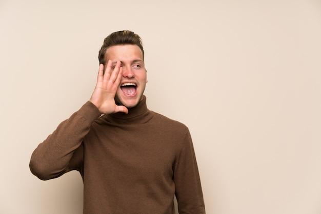 Homem bonito loiro sobre parede isolada gritando com a boca aberta Foto Premium