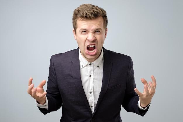Homem bonito louco de raiva em pé gritando ou berrando Foto Premium