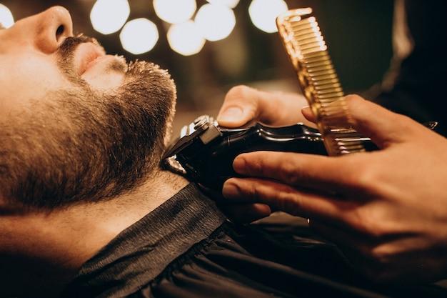 Homem bonito na barbearia barbeando a barba Foto gratuita