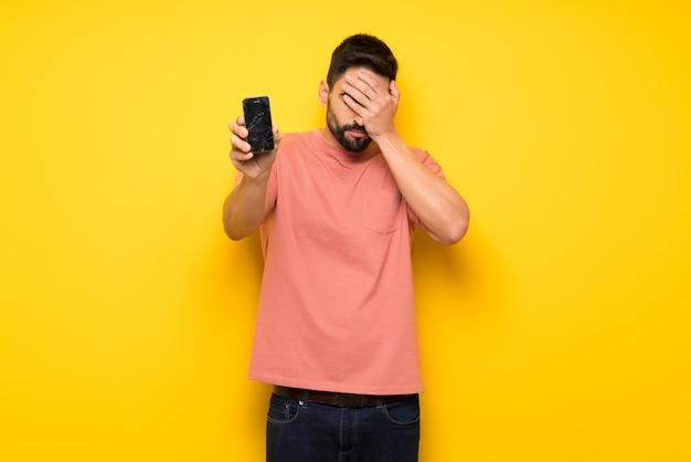 Homem bonito na parede amarela com incomodado segurando smartphone quebrado Foto Premium