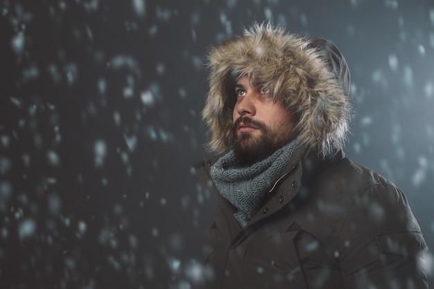 Homem bonito na tempestade de neve Foto gratuita