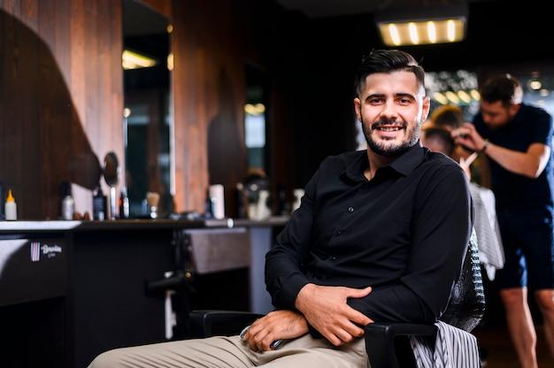 Homem bonito no salão de cabeleireiro de frente para a câmera Foto gratuita