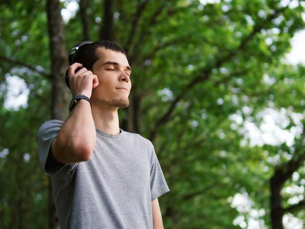 Homem bonito nos auscultadores que escuta a música ao ar livre. Foto Premium