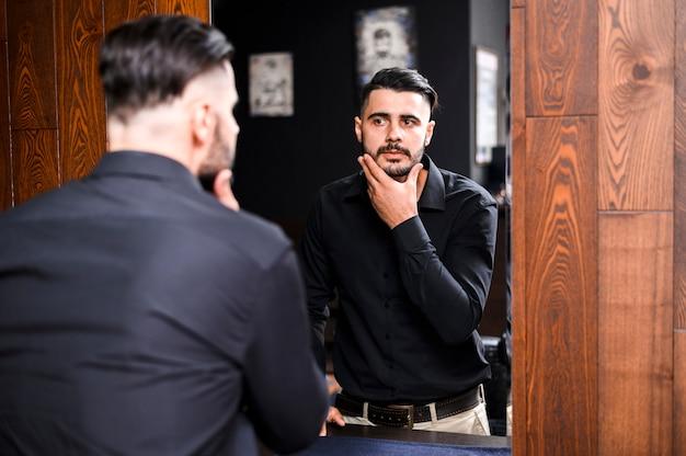 Homem bonito olhando no espelho Foto gratuita