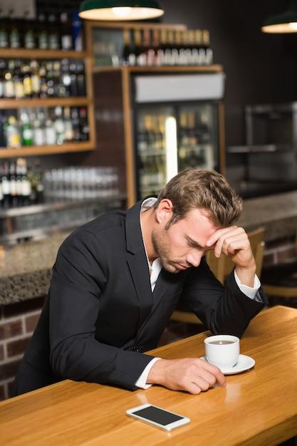 Homem bonito olhando para smartphone e tomando um café Foto Premium