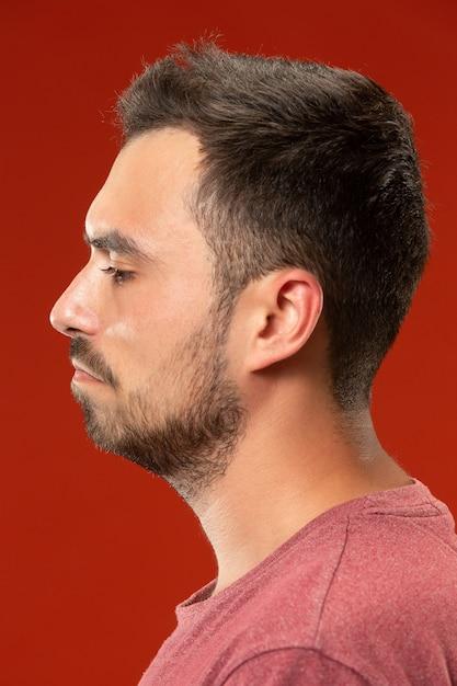 Homem bonito olhando surpreso e confuso isolado no vermelho Foto gratuita