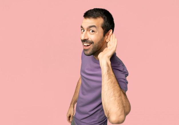 Homem bonito ouvir algo, colocando a mão sobre a orelha no fundo rosa isolado Foto Premium