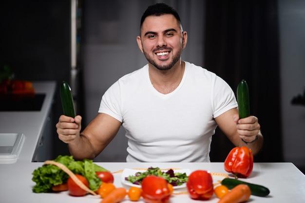 Homem bonito para comer comida vegetariana saudável em casa. Foto Premium