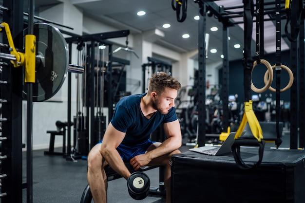 Homem bonito, praticar pesos de musculação no ginásio e assistir mídia no laptop Foto Premium