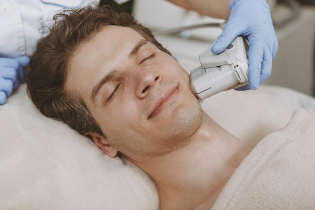 Homem bonito, recebendo tratamento de pele facial Foto Premium