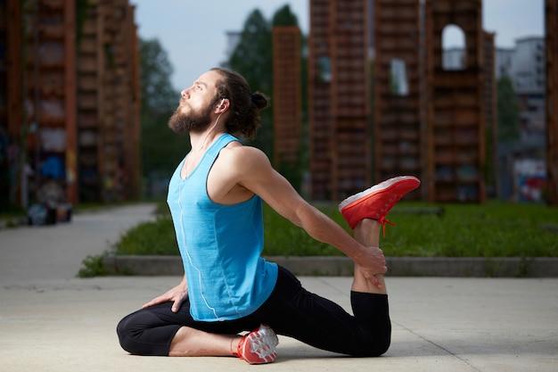 Homem bonito relaxado fazendo exercícios de ioga Foto Premium