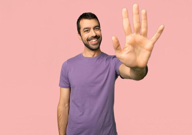 Homem bonito, saudando com a mão com uma expressão feliz no fundo rosa isolado Foto Premium