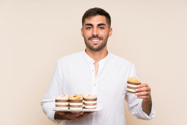 Homem bonito, segurando o bolo muffin sobre parede isolada Foto Premium