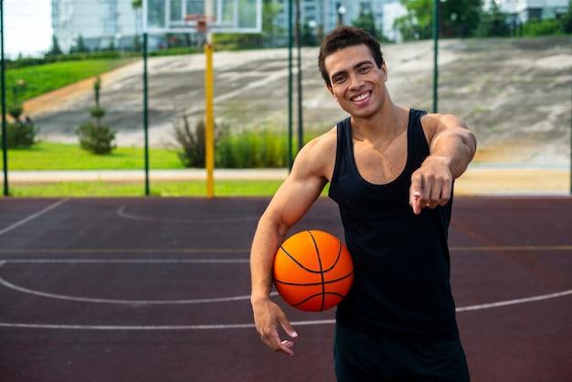 Homem bonito, segurando uma bola de basquete tiro médio Foto gratuita