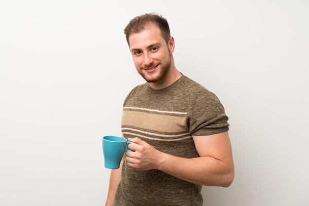 Homem bonito, segurando uma xícara de café quente Foto Premium