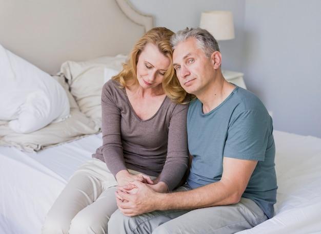 Homem bonito sênior e mulher sentada na cama Foto gratuita