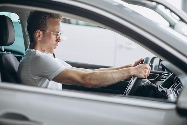 Homem bonito sentado em um carro Foto gratuita