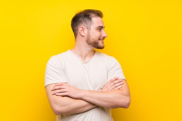 Homem bonito sobre fundo amarelo, olhando para o lado Foto Premium