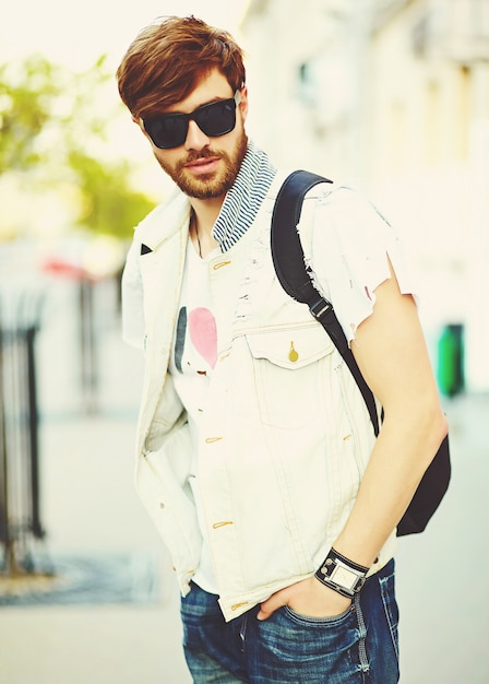 Homem bonito sorridente engraçado hipster em roupas de verão elegante na rua em óculos de sol Foto gratuita