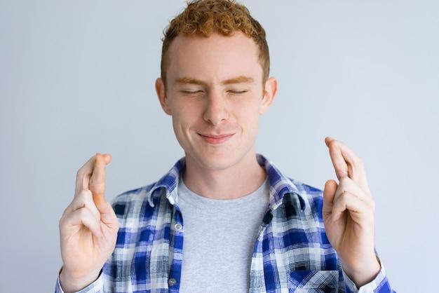 Homem bonito sorridente, mostrando o gesto de dedos cruzados Foto gratuita