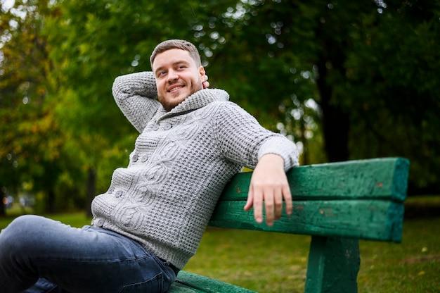 Homem bonito, sorrindo em um banco no parque Foto gratuita