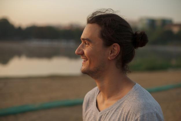 Homem bonito, sorrindo no parque Foto gratuita