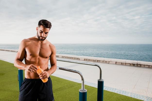 Homem bonito, tendo uma pausa e hidratar durante o treino Foto gratuita