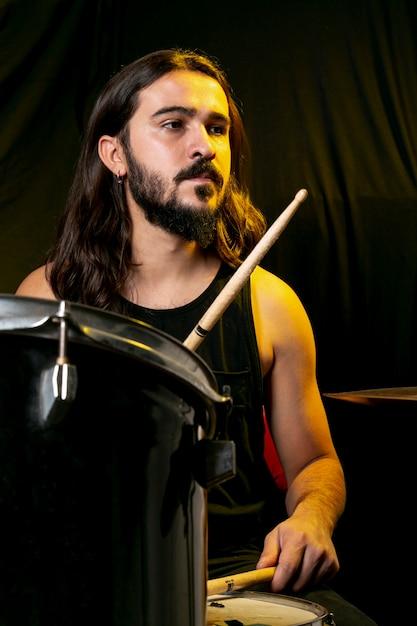 Homem bonito tocando bateria com varas Foto gratuita
