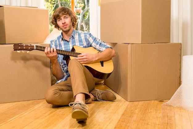 Homem bonito tocando guitarra com caixas de mudança em sua nova casa Foto Premium