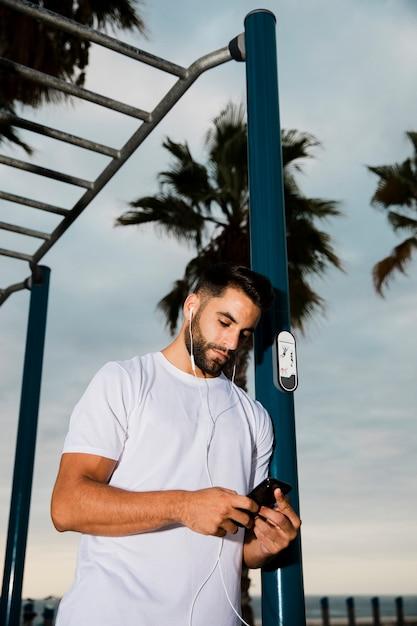 Homem bonito tocando música no celular após treino Foto gratuita