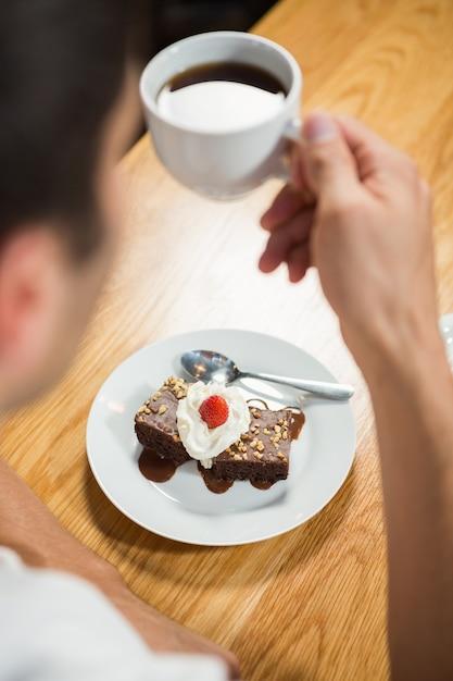 Homem bonito, tomando um brownie e um café Foto Premium