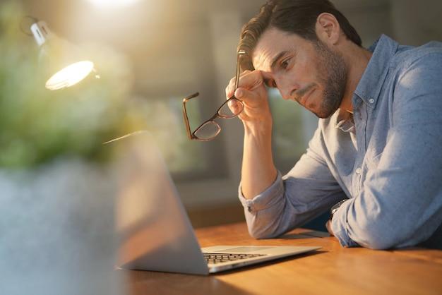 Homem bonito, trabalhando até tarde em casa Foto Premium
