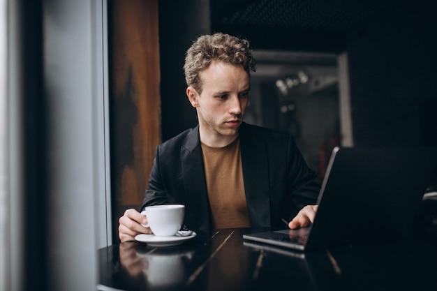 Homem bonito, trabalhando em um computador em um café e beber café Foto gratuita
