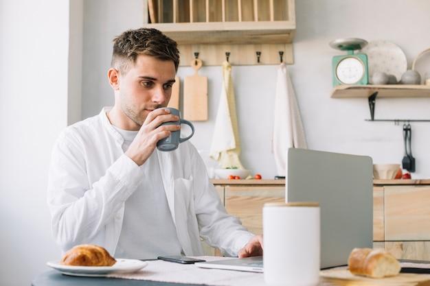 Homem bonito, trabalhando no laptop bebendo café na cozinha Foto gratuita