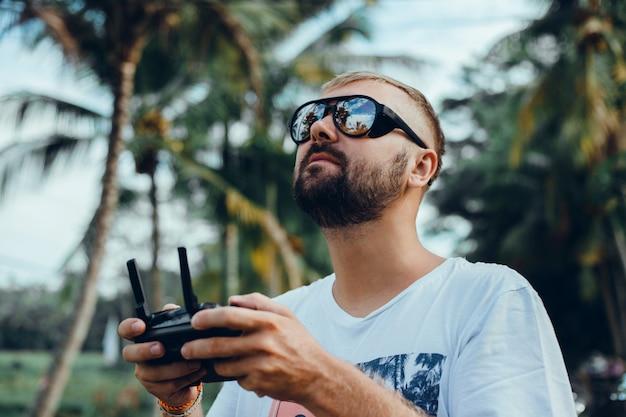 Homem bonito usa drone na rua Foto gratuita