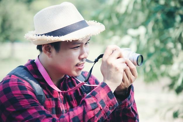 Homem bonito usando a câmera na natureza do curso Foto gratuita