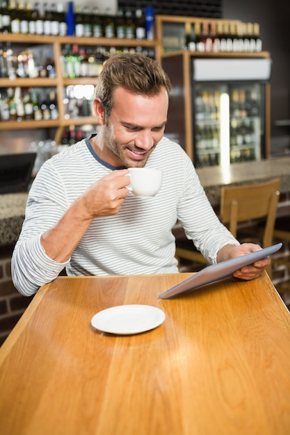 Homem bonito usando computador tablet e tomando um café Foto Premium