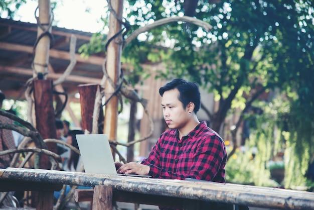Homem bonito usando laptop na natureza viagens Foto gratuita
