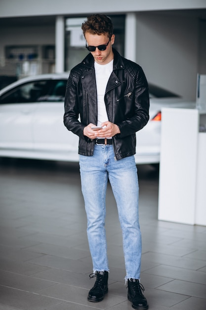 Homem bonito, usando o telefone em um showroom de carro Foto gratuita