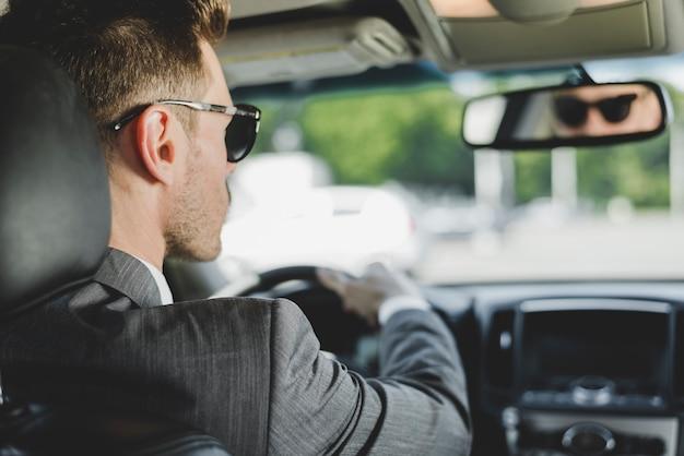 Homem bonito, usando óculos escuros, olhando para o espelho retrovisor no carro Foto gratuita