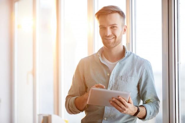 Homem bonito usando tablet na luz solar Foto Premium