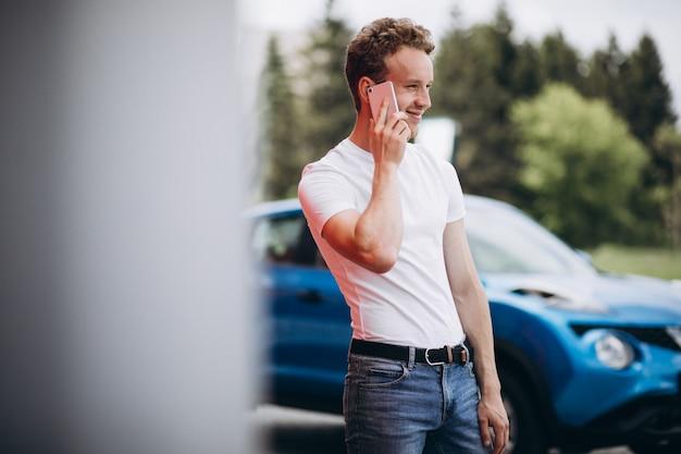 Homem bonito, usando telefone pelo carro Foto gratuita