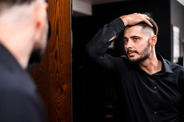 Homem bonito, verificando seu novo estilo de cabelo Foto gratuita