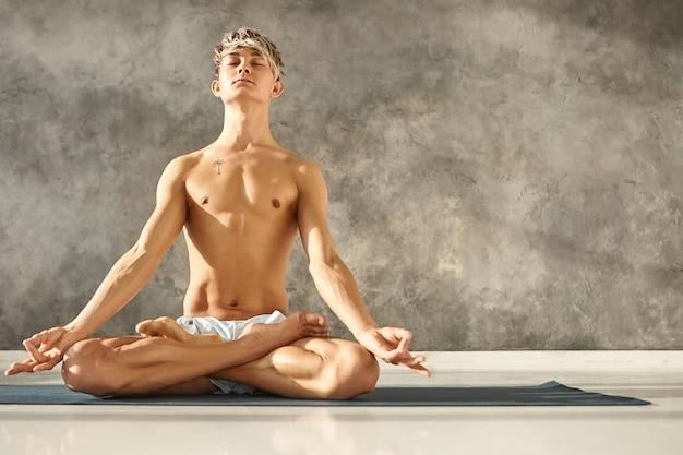 Homem branco jovem e iluminado posando sem camisa e descalço na academia, com expressão facial calma e pacífica, meditando com os olhos fechados, sentado no tapete em posição de lótus, mãos em gesto de mudra Foto gratuita