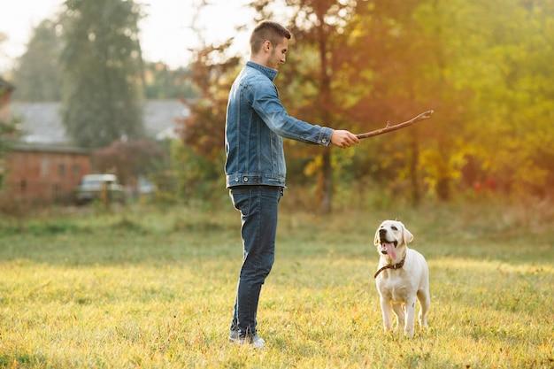Homem brincando com cachorro labrador no parque ao pôr do sol Foto gratuita