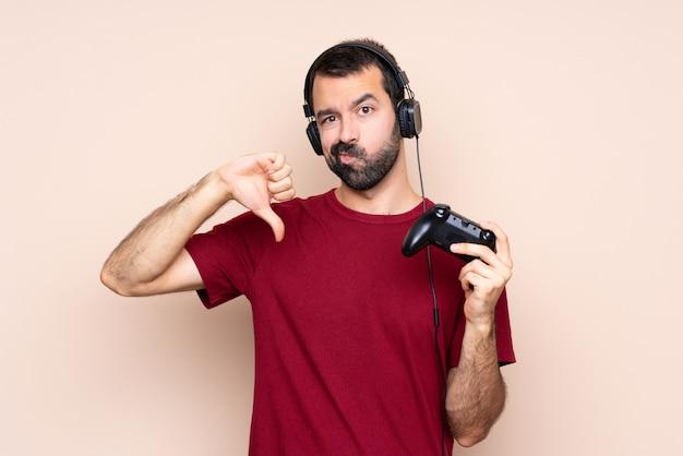 Homem brincando com um controlador de videogame sobre parede isolada, mostrando o polegar para baixo Foto Premium