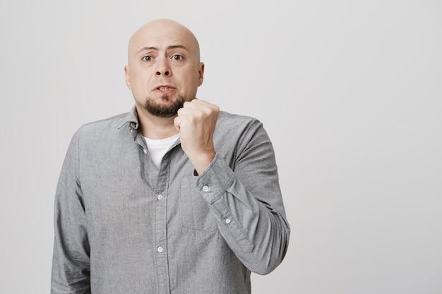 Homem calvo adulto repreendendo com punho erguido, ameaçando Foto gratuita