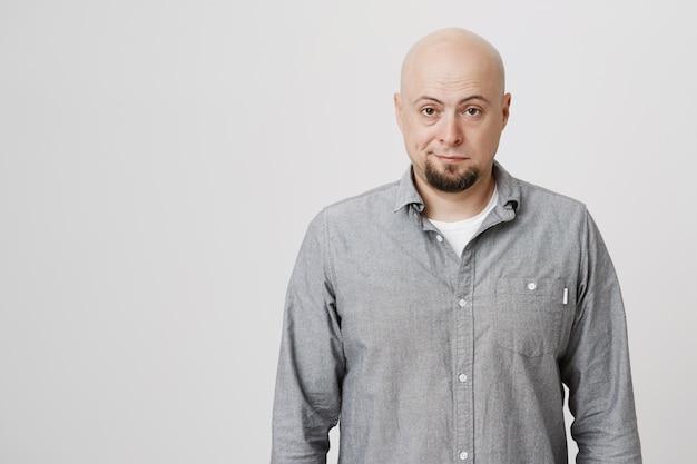 Homem calvo cético e relutante olha com irritação Foto gratuita